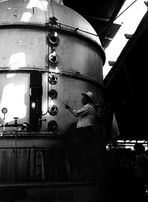 Trabajador junto a un alambique de industria azucarera, en Jalisco