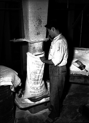 Trabajador llena un costal con azúcar, en las instalaciones de un ingenio azucarero
