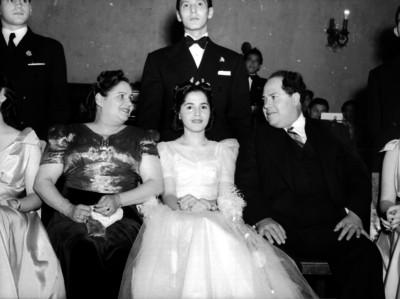 Agustín Arroyo Ch. con su esposa e hija durante un evento social en un salón