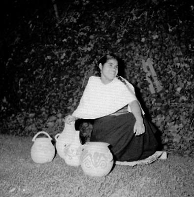 Mujer portando un traje folclórico sentada junto a unos cántaros, retrato
