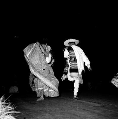 Pareja con trajes regionales interpretan un baile folclórico
