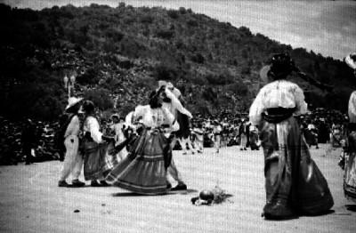Parejas con trajes Zapotecas ejecutan un baile en la Guelaguetza