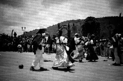 Gente observa a parejas con trajes Zapotecas al ejecutar un baile