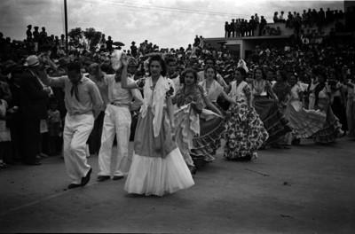 Parejas ataviadas con diversos trajes mestízos el ejecutar un baile en el festival de la Guelaguetza
