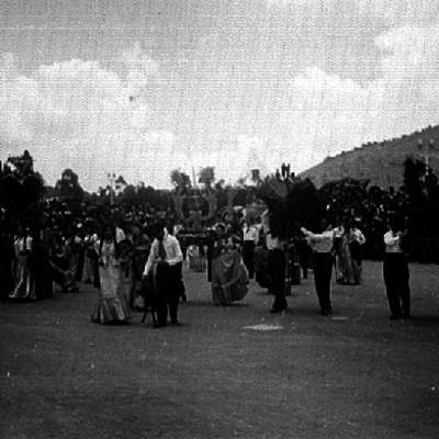 Hombres y mujeres vestidos con trajes Mixtecos lavantan arreglos florales en el festival de la Guelaguetza