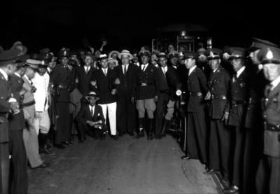 Asuero, médico, rodeado de gente en la estacón de ferrocarril Buenavista, retrato de grupo