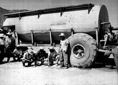 Trabajadores conversando junto a una pipa de agua