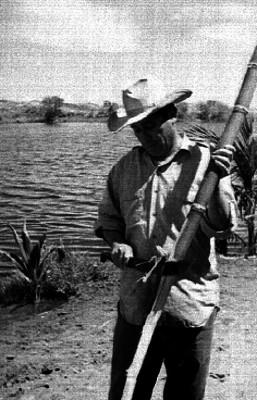 Hombres peleando una bara de bambú a la orilla de un río en el estado de Tabasco