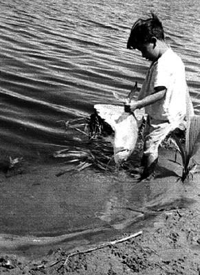 Niño cargando un pescado a la orilla de un río en el estado de Tabasco