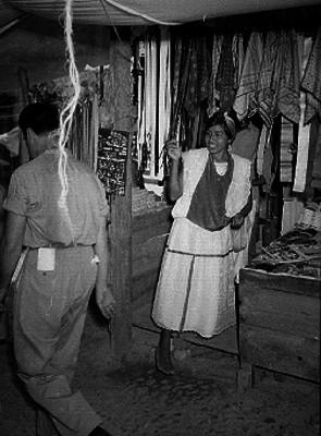 Mujer totonaca en un puesto con venta de paliacates