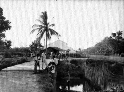 Campesinos conversando en un puente rústico sobre un río de un poblado del estado de Veracruz