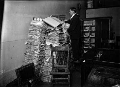 Hombre lee sobre una pila de libros de un archivo