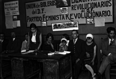 Mujer lee documento durante una reunión de asociaciones políticas