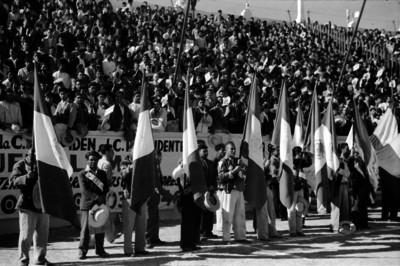 Líderes obreros y campesinos portan banderas en un acto público