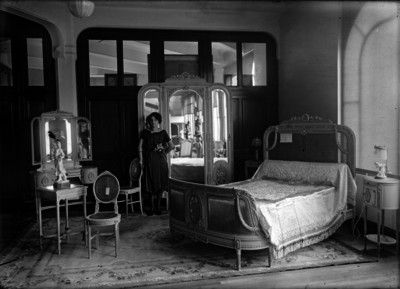 Mujer posa junto a muebles para recámara en interior de almacén