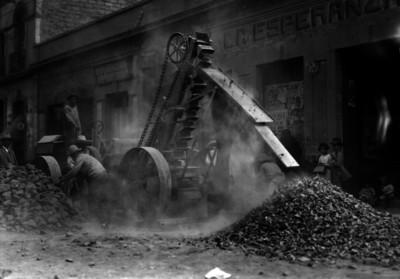 Trabajadores conducen maquinaria pesada para levantar escombro