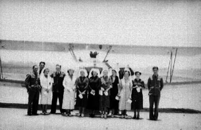 Pilotos aviadores en campañia de mujeres elegantes, retrato