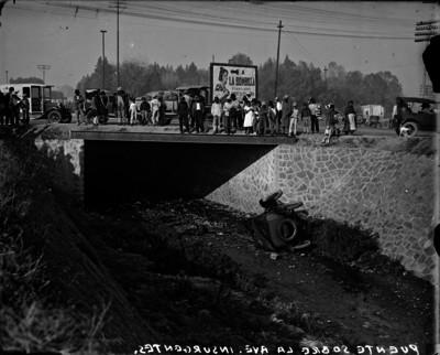 """Gente observa un automóvil chocado debajo de un """"puente sobre la ave. Insurgentes"""""""