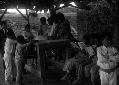 Niños en edad escolar leen y aprenden artes manuales, maestro observa