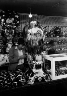 Hombre y niño observan jarrón y objetos de cerámica en una feria