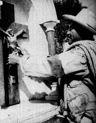Hombre colocando crucifijo en lápida de una tumba