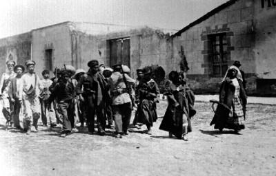 Soldaderas acompañadas de militares transitan por una calle