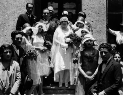 Novios acompañados de gente, en las escaleras de una casa