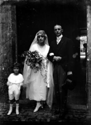 Pareja de novios acompañados de un niño en el marco de una puerta, retrato