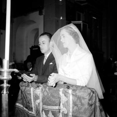 Daniel Kuri Breña y María Cristina Romero de Terreros leyendo un rosario hincados ante un altar durante su boda en una iglesia