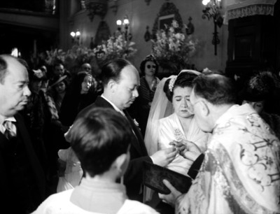 Novio colocando la argolla matrimonial a la novia durante la boda religiosa
