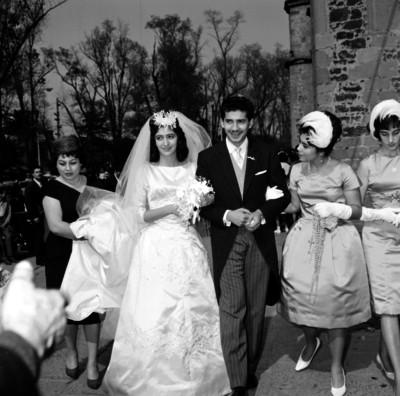 Novios caminando frente a una iglesia acompañados de familiares, durante su boda