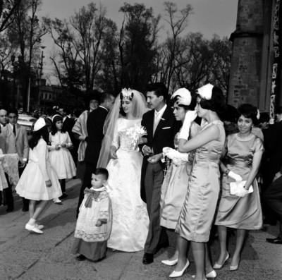 Novios caminando frente a una iglesia, acompañados de familiares y amigos durante su boda