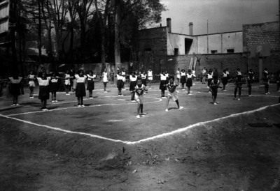 Niños y niñas realizando ejercicios de una tabla gimnástica, en la cancha de básquetbol de una escuela
