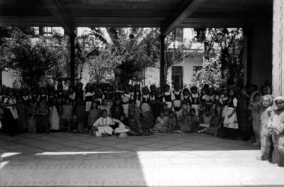 Niños y niñas vestidos con diferentes trajes regionales, bajo el portal de una escuela, retrato