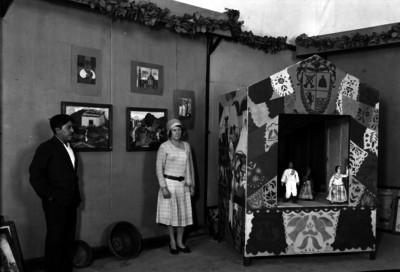 Pareja observando una exposición de pinturas, cerámica y un teatro de títeres, en un salón