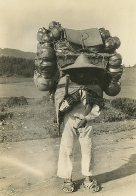 Hombre indígena carga sobre su espalda cántaros