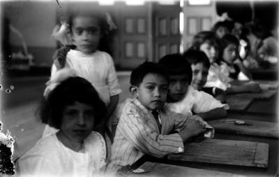 Niños sentados en mesabancos en el interior de un salón de clases