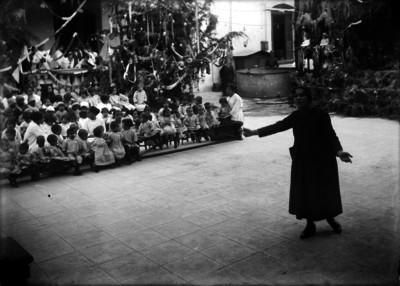 Maestra declamando en un festival preescolar, en el patio de una escuela