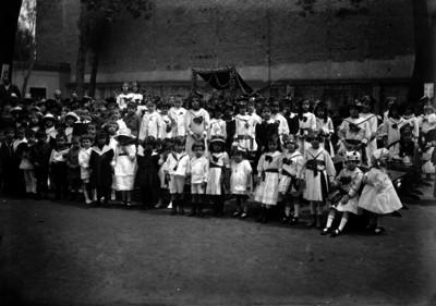Niños y niñas (alumnos de una escuela) en un patio, retrato de grupo