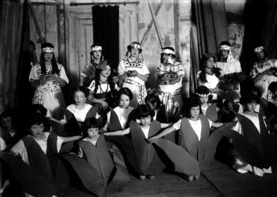 Niñas vestidas de indígenas y flores durante una representación teatral de un festival escolar, en un auditorio