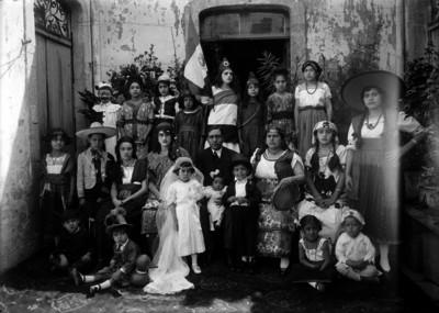 Maestros y alumnos vestidos de indígenas mexicanos durante un festival escolar en el patio de una escuela, retrato de grupo