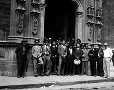 Alumnos y maestros parados en la entrada del Colegio de San Ildefonso, retrato de grupo