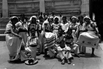 Niños y niñas con traje mestizo de la zona mixteca en un festival escolar en un salón, retrato de grupo