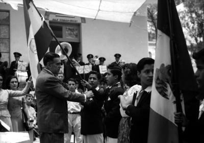 Niño recibiendo la bandera durante la ceremonia