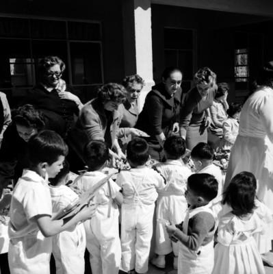 Mujeres elegantes entregando juguetes a niños y niñas durante un festival del día del niño