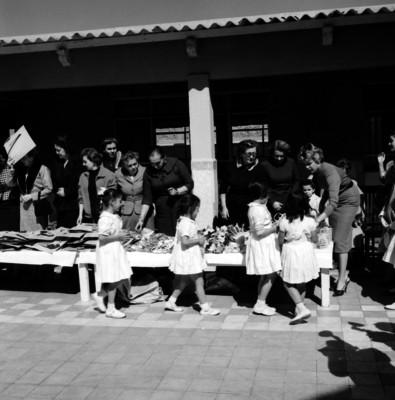 Niñas recibiendo dulces y juguetes de mujéres elegantes durante la celebración del día del niño en una escuela