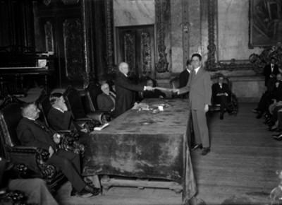 Miembro de la colonia española entregando un documento en una oficina