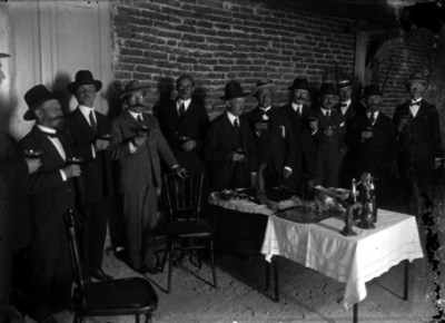 Miembros de la colonia española durante un brindis en el interior de una habitación, retrato de grupo