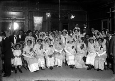 Mujeres vestidas de españolas y hombres en un salón, retrato de grupo