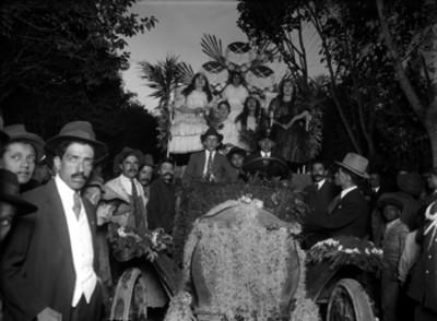 Personas con trajes folclóricos en un carro alegorico durante festividades de la colonia española